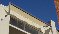 Balcony structure covered with shade sail using track