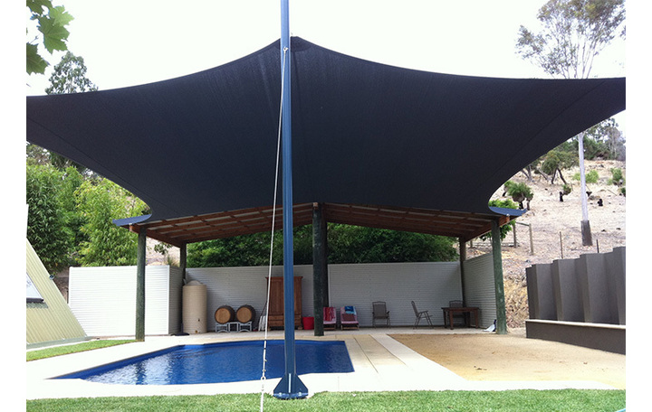 Photograph of 6 sided large sail with heavy duty wood poles and steel posts. Fabric is Comshade navy blue.